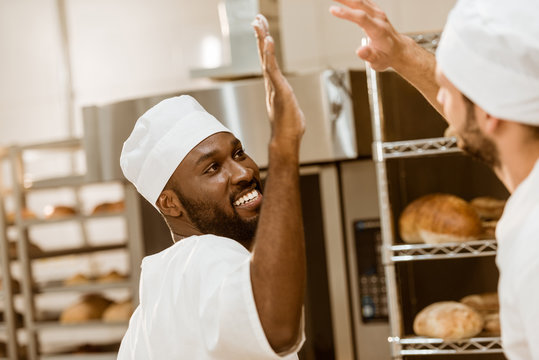 handsome young bakers giving high five at baking manufacture