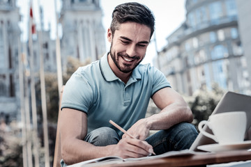 Preparing for work. Low angle shot of a bearded businessman grinning broadly while sitting in a cafe and taking notes with a pencil.