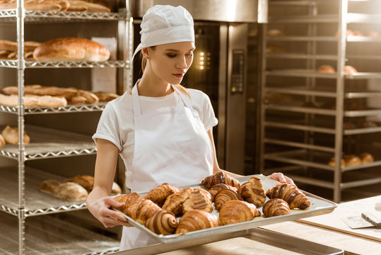 attractive female baker holding tray with fresh croissants on baking manufacture