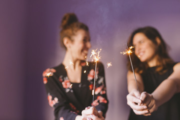 two young beautiful women having fun with sparkles indoors. Purple background. Casual clothing. Fun, happiness and lifestyle