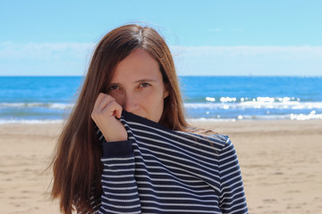 woman on the beach covers her mouth with the striped sailor jersey