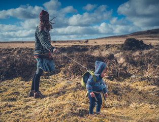 Young mother walking on the moor with her toddler