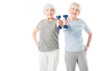 Two senior sportswomen doing exercise with dumbbell isolated on white