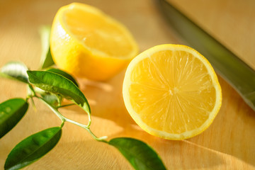 Cut lemon with green leaves and a knife on a wooden board lit by the sun