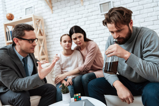 Adult bearded father, holding bottle of whiskey, sits with family at reception of psychologist.