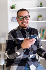 Smiling man in glasses with smartphone looking at the camera