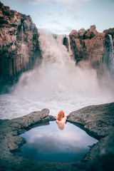 Rear view of a woman in a rock pool looking at Aldeyjarfoss waterfall, Highlands, Iceland