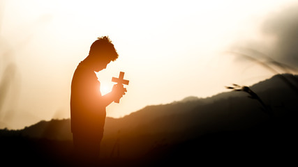 Young holding christian cross with light sunset background