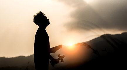 Young holding Bible book and christian cross with light sunset background