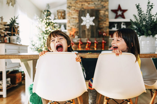 Boy and girl sitting at the dining table messing about at Christmas