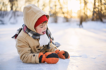 Boy lying on a frozen lake licking a piece of ice