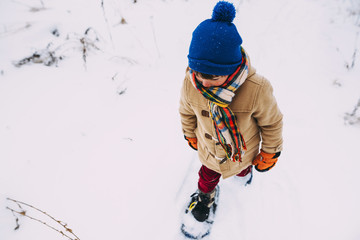 Boy walking in the snow wearing snowshoes