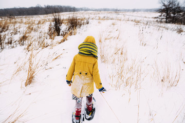 Girl walking in the snow wearing snowshoes