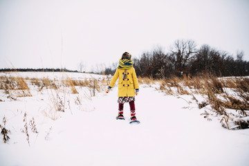 Girl standing in the snow wearing snowshoes