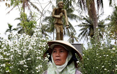 A woman arranges flower in front of a statue in a museum during the 50th anniversary of the My Lai massacre in My Lai village