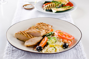 Grilled chicken breast with tabbouleh salad and grilled vegetables on white