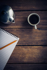 Cup of coffee, coffee pot, notepad and pencil