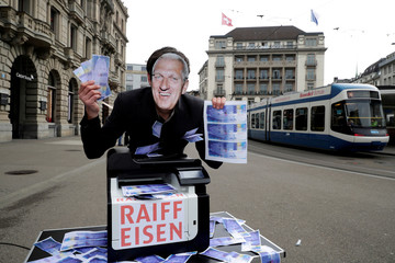 Raffael Wuethrich, masked with the face of former CEO Pierin Vincenz of Raiffeisen bank, holds fake money next to a printer during a demonstration by The Swiss Sovereign Money Initiative, in Zurich