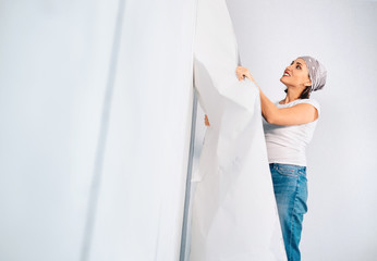 Woman prepare room for renovation, take off wallpapers from wall