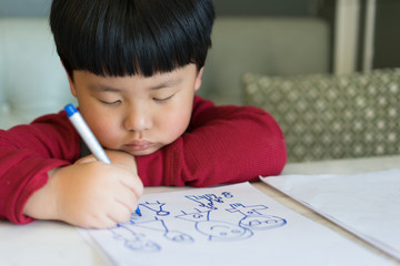 A Asian boy is drawing a picture.