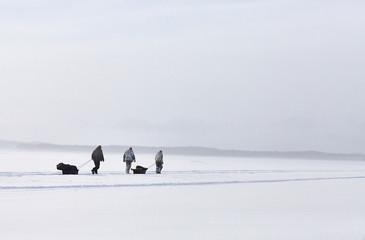 Winter fisherman's hiking on lake ice at sunset