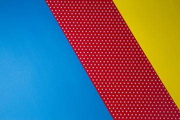 Abstract geometric blue, yellow and red polka dot paper background.