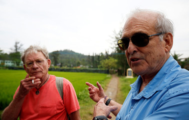 U.S. Army photographer Ronald Haeberle (R) talks with U.S. veteran Billy Kelly on the road where he took photos 50 year ago, during the 50th anniversary of the My Lai massacre in My Lai village
