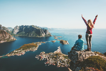 Couple family traveling together on cliff edge in Norway man and woman lifestyle concept summer vacations outdoor aerial view Lofoten islands Reinebringen mountain top Fototapete
