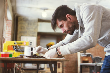 A young master paints a wooden piece in a handmade workshop