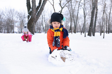 Happy children in snowy park on winter vacation