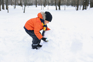 Cute boy making snowman in park on winter vacation