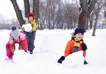 Happy children making snowman in park on winter vacation
