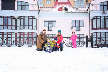 Happy family sledding in snowy park on winter vacation