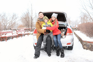 Happy family sitting in car trunk on winter vacation