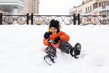 Cute boy having fun in snowy park on winter vacation