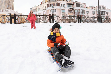 Cute boy sledding in snowy park on winter vacation