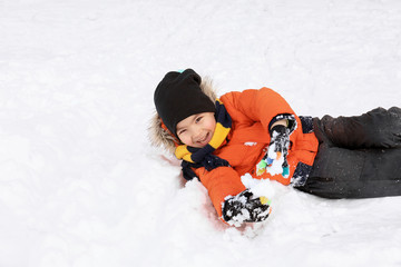 Cute boy in snowy park on winter vacation