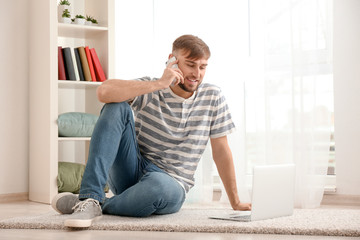 Young man talking on mobile phone while working with laptop at home