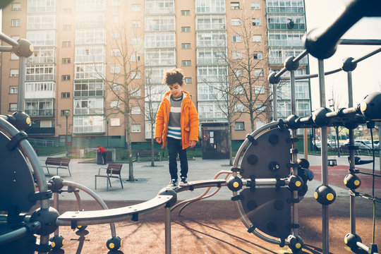 Little boy playing in the balance bar in a playground