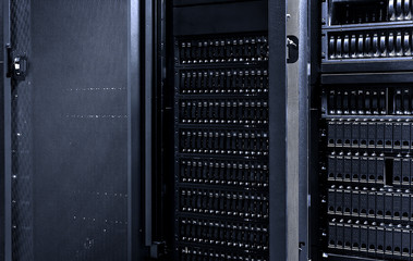 Dark server room data center storage with with open door of mainframe