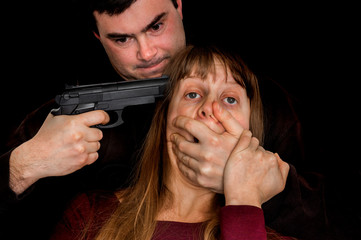 Man with a handgun aiming on a head his victim
