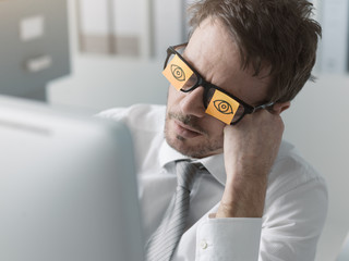 Lazy office worker wearing sticky notes over his glasses