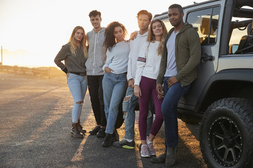 Young adult friends on a road trip standing by their jeep