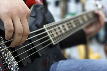 close up on the fingers of musician playing bass guitar on the stage
