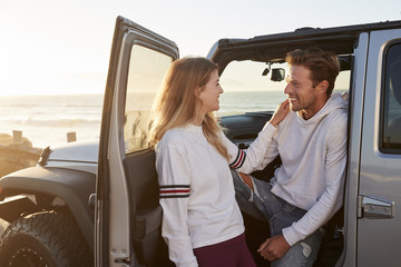 Young couple on road trip looking at each other by their car