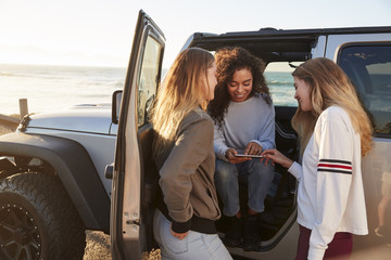 Three girlfriends planning road trip with tablet computer