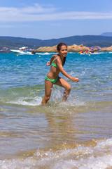 Girl running and splashing on the shallow beach