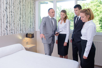 hotel service housekeeping workers and manager in a hotel room