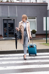 businesswoman with suitcase and umbrella crossing road on street