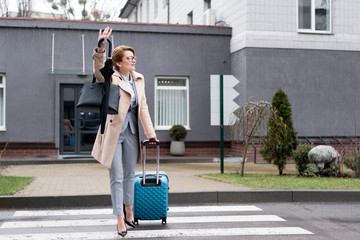 businesswoman with suitcase and umbrella calling for taxi on street